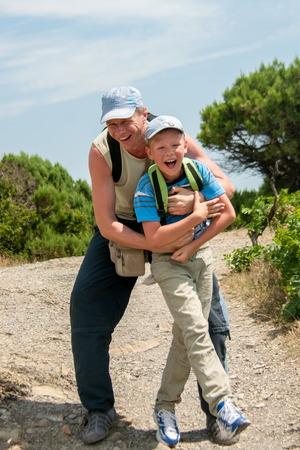 affectionate action: father and son having fun outdoors in caps and backpacks summer day Stock Photo