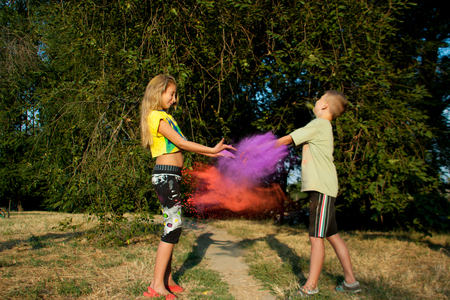 boy and girl on the nature sprinkled with Holi colors