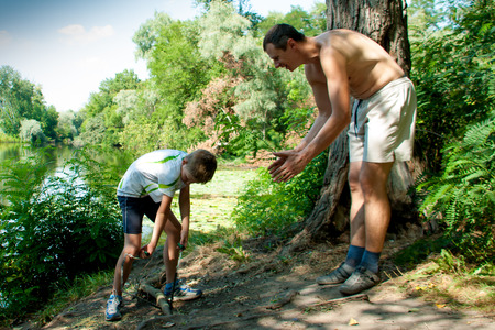 sawing: father and son sawing wood near the river summer day