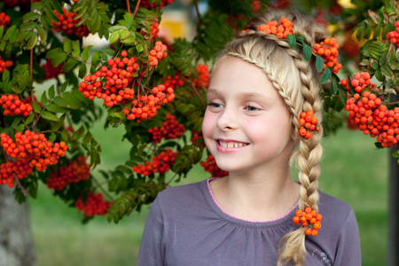girl in nature with beautiful hairstyle with elements rowan Stock Photo