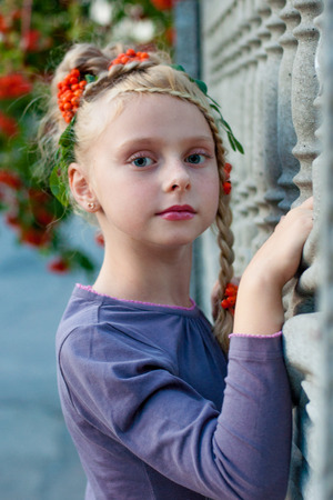 girl near a fence of concrete with a beautiful hairstyle with elements rowan Stock Photo