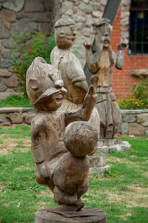 wooden sculpture of three Cossacks on the building background bright day