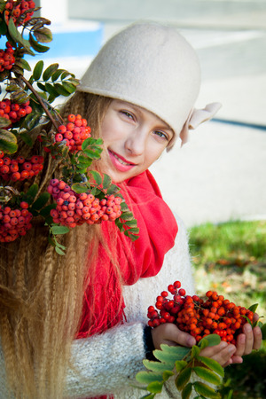 rowanberry: girl stands near the rowan with a red scarf in white clothes autumn Stock Photo