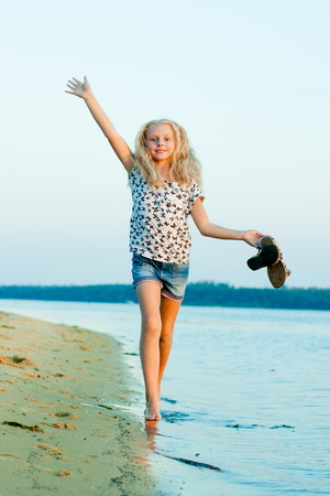 girl running on the beach at the water barefoot with shoes in hand