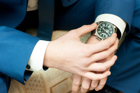 white sleeve: A man in a jacket and a white shirt with a watch on his arm