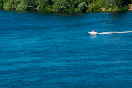 river: A small boat sails along the river on a summer sunny day