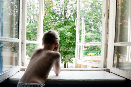 Boy without outer clothing looks at the open window