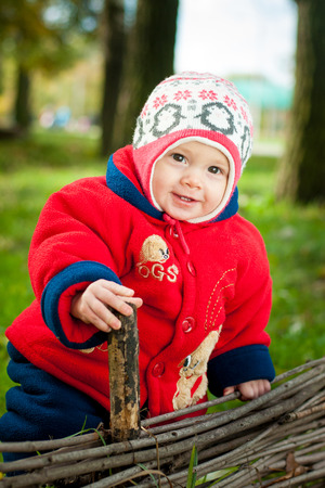 the child is standing on the street near the wooden fence in autumn Stock Photo