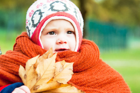 child with an armful of leaves and with a big orange scarf
