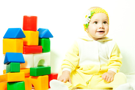 the child is sitting near colorful cubes indoors