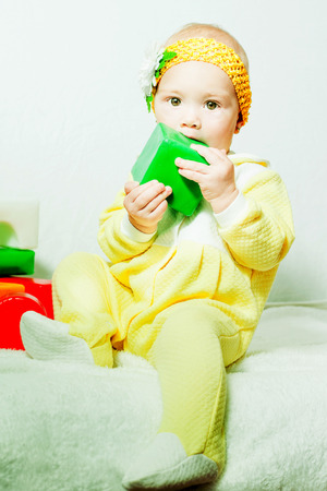 baby gnawing a toy green cube indoors