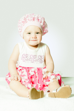 child in a cap sits on a white background
