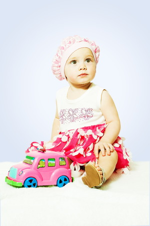 little girl sitting with pink toy car indoors Stock Photo