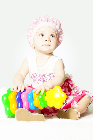 little girl sitting with toy pyramid indoors Stock Photo