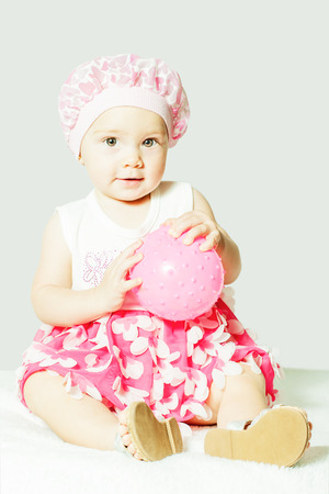 little girl sitting with ball in hands indoors