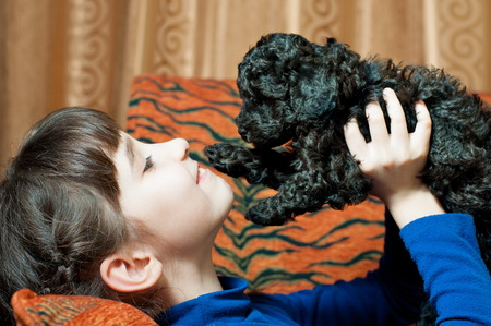 the girl with the black poodle puppy breed indoors