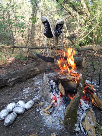 sneakers on a stick near fire in the open air Stock Photo