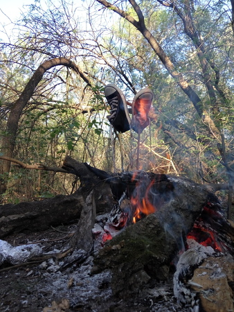 sneakers on a stick near a campfire in the open air