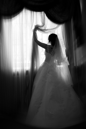 silhouette of the bride near the window from the back