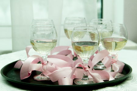 glasses with champagne on a tray tied with a pink ribbon Stock Photo