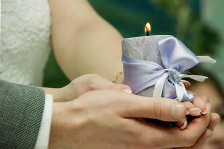 man and woman holding a burning candle in their hands