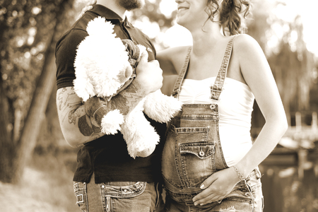 pregnant woman and a man with a bear cub in his hands outdoors Stock Photo