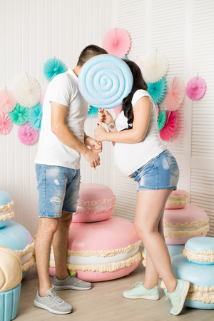 pregnant woman and a man hid their face with candy on a stick