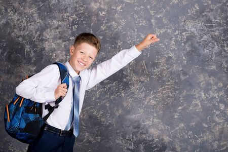 boy in a white shirt and tie on a gray background with a backpack