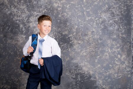 boy in white shirt and tie with jacket on his hand posing Stock Photo