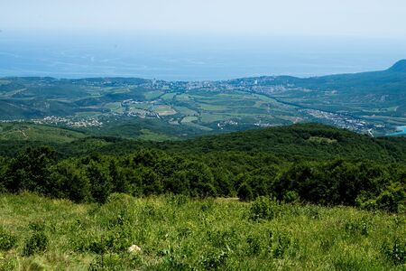 view from the mountain to the forest and the city on a clear summer day Stock Photo