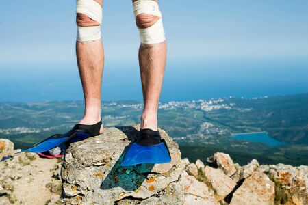 male legs in flippers in the mountains against the background of the sea Stock Photo