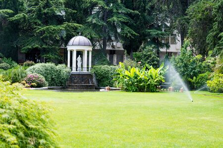 a beautiful park with a sculpture of a priestess of secret revelations Papess