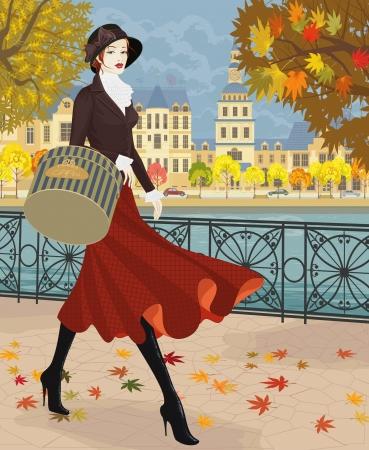 美しい若い女性は秋の都市の堤防に沿って歩く