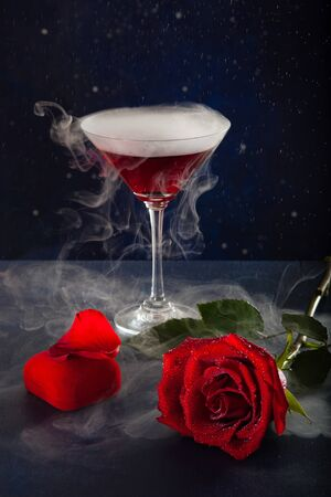 Midnight glass of mistic drink, rose and box with a ring