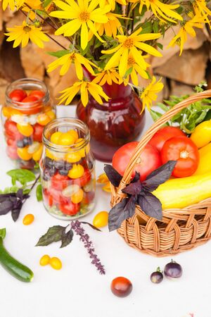 Bouquet of flowers and basket with autumn crop of seasonal vegetables