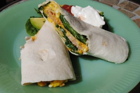 卵、チーズ、ハム、ほうれん草ビンテージ緑ジェーンレイ プレート、サルサ、サワー クリーム、アボカド側の朝食ブリート