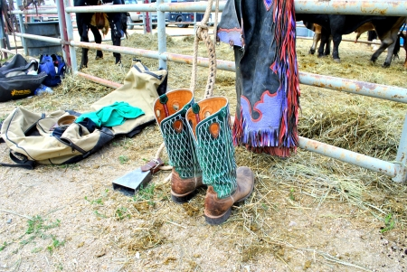 Cowboy boot, chaps and gear at country rodeo with bulls in background behind rusted fence
