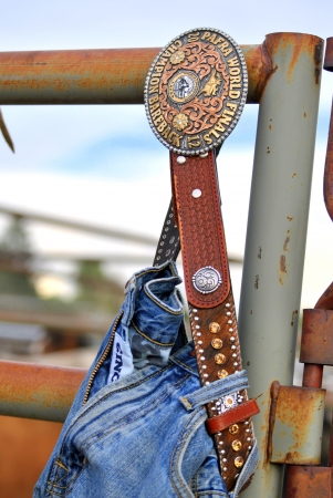 scuffed: Close up of Professional Armed Forces Rodeo Associan belt buckle with blue jeans on a rusted fence at country rodeo