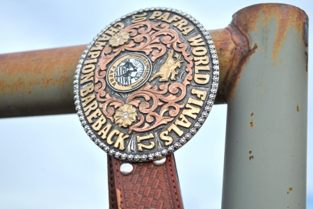 Professional Armed Forces Rodeo Association Buckle up close on rusted fence at country rodeo