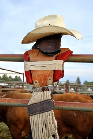 buckaroo: Straw cowboy hat sitting atop saddle on rusted fence at country rodeo Stock Photo