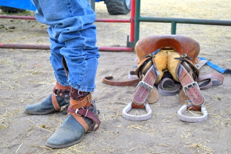 Cowboy wearing cowboy boots and buckles next to staddle at country rodeo  photo