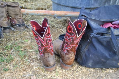 duffle: Brown and red leather Cowboy boots on ground next to a duffle bag at a country rodeo