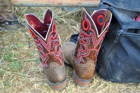 buckaroo: Pair of cowboy boots and duffle bag on the ground at rural rodeo