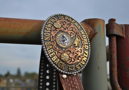 Professional Armed Forces Rodeo Association buckly hanging on a rusted fence up close