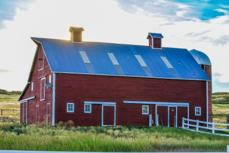sund: Barn in a rural setting under bright setting sund with sun behind building  Editorial