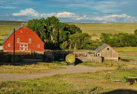Red bard in rural field with outbuildings and round bale of hay