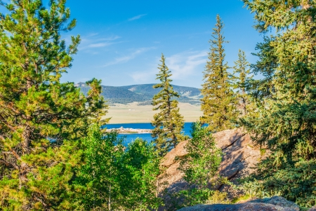 Fir and pine trees surrounding a view of a mountain lake with mountains in the distance   Stock Photo
