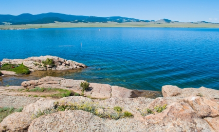 Mountain lake, rocks and shoreline with mountain range  in background of crystal clear water