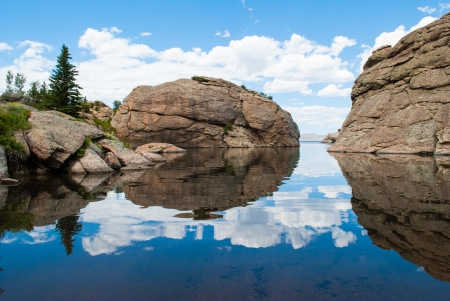 Mountain boulders, rocks, puffy white clouds in a bright blue sky reflected in a mountain lake  photo