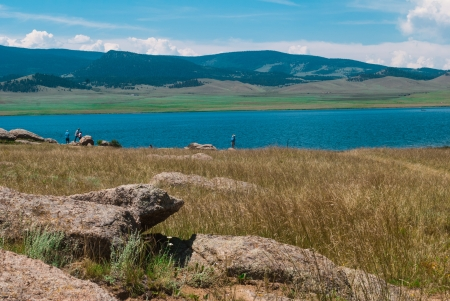Blue mountain lake, high plains grasses and rocks in the foreground with mountain range and white clouds in the distance  photo